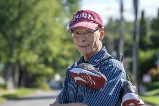 Gary Geiger stands in the roadway with his running shoes in Scotia on Sept. 1.