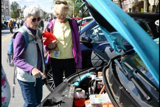 Elizabeth Stehl of Niskayuna points to the engine of a 2020 Chevy Bolt EV outside Schenectady City Hall at the Schenectady Green Market on Se[t 26, 2021,with Ellen Hiscox, of Schenectady, right, as part of more than 20 cars on display to kick off National Drive Electric Week to promote the use of electric vehicles.