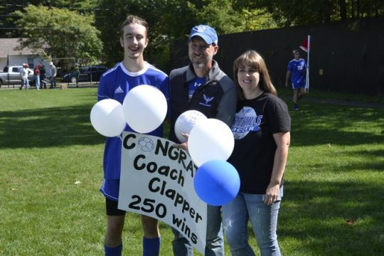 Northville boys' soccer coach Steve Clapper, center, poses with his son, Caleb, left, and wife, Amy, right after earning his 250th career victory in a 4-1 win over Loudonville Christian on Saturday.