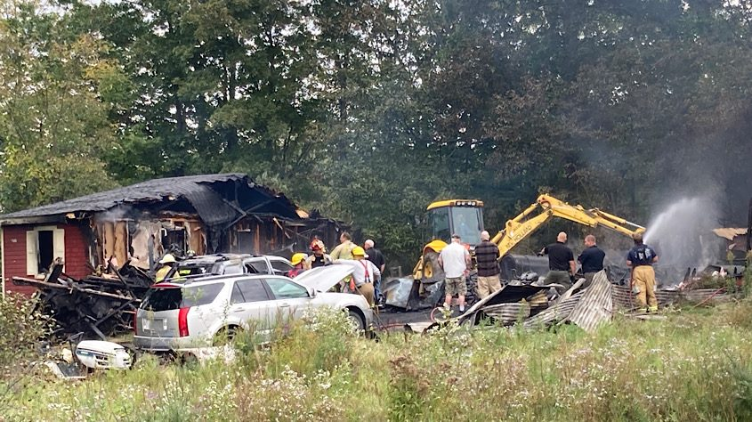 Fire crews work with an excavator to safely bring down a house and extinguish the fire that destiny the home.