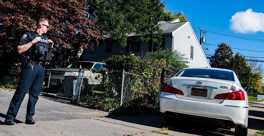 A police officer watches over a car on the sidewalk Wednesday morning near the intersection of Schenectady and Hamilton streets.