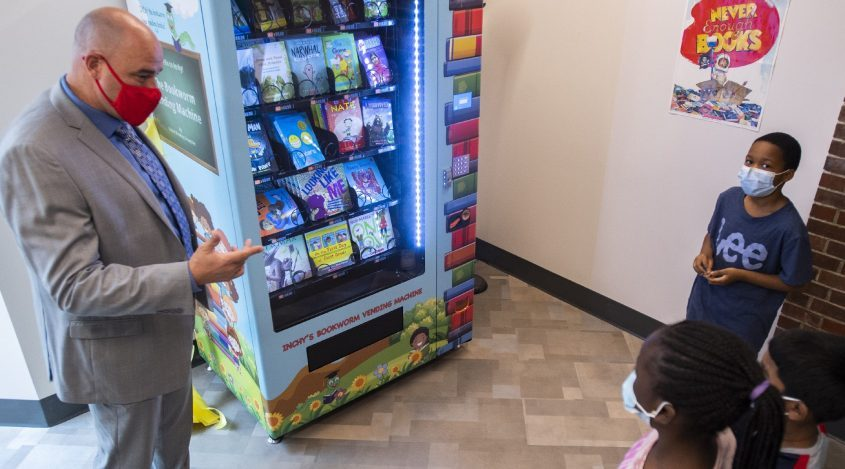 Schenectady City Schools superintendent Anibal Soler, left, talks to Martin Luther King Elementary School students Cecilia Ospitan, Mahnendra Ramdaill and Amari Brown, all 8, about the importance of books and reading before they tried out the new book vending machine in the school's waiting room on Sept. 29, 2021.