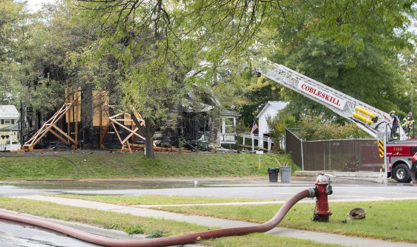 A Cobleskill ladder truck operates at the scene of a fire at 395 Mian Street in the village of Schoharie Wednesday.