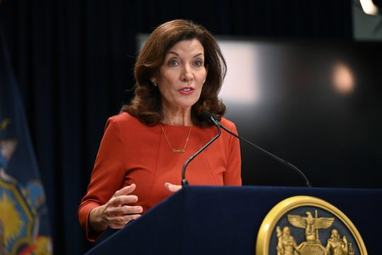 """GOVERNOR'S OFFICEGov. Kathy Hochul, wearing a necklace pendant that reads """"vaxed,"""" speaks to reporters about COVID vaccination for healthcare workers on Thursday in New York City."""