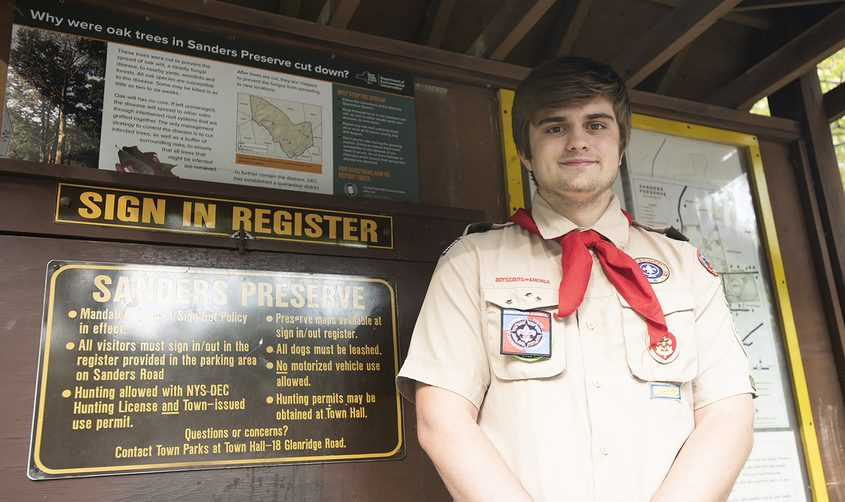 Troop 67 Eagle Scout Nick Favata of Scotia stands at the Sanders Preserve sign in Glenville on Sept. 27. His eagle project was a redirection and signage of the green trail around a portion of private property in the preserve.