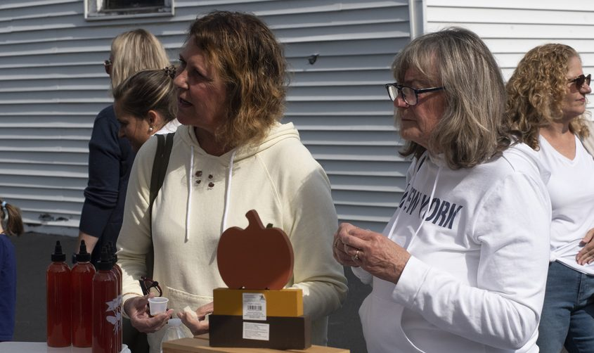 Susan Kutcher of Glenville, left, and Joyce Callahan of Edinburgh take in some of the offerings at the Baucy Be's Honey Hot Sauce tent outside the Broadalbin Hotel Saturday morning during the Fulton County Outdoor Adventure Day - A Craft Fair with Outdoor Flair in Broadalbin.