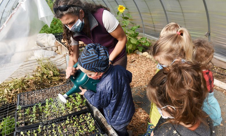 Pre-K student Milo Lamb, 4, helps water plants with Owner/lead teacher Aaren Harris in the greenhouse at the new school Little Wings Farm in Greenfield Center onSept. 29.