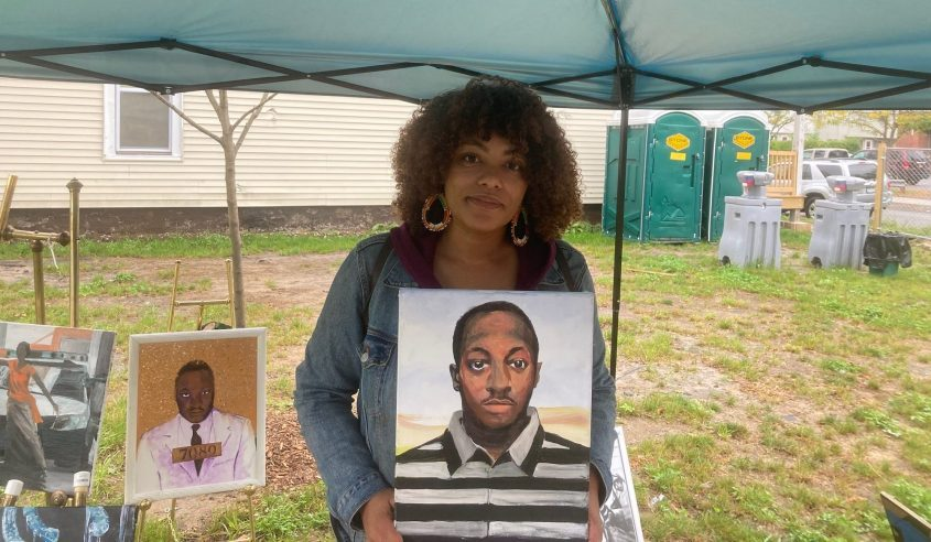 Local artist Bianca DiLella holds her painting of Kalief Browder during the Oct. 3, 2021, African Market in the Hamilton Hill Arts Center's sculpture park.