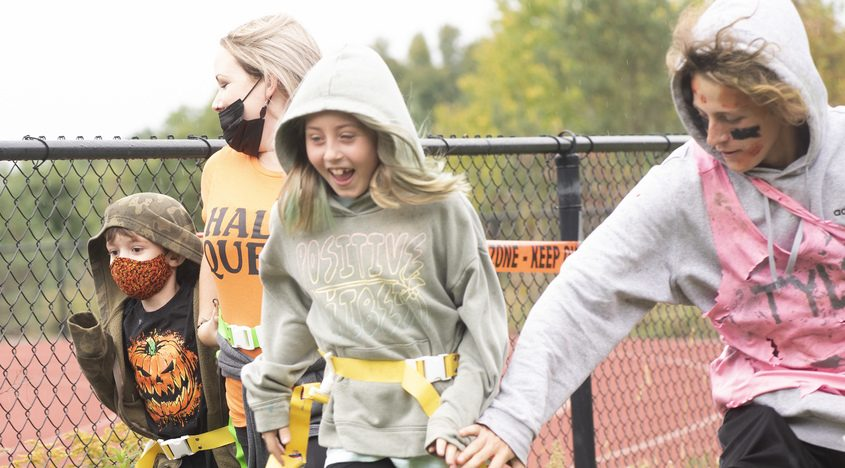 Tyler Busch, 17, of Delanson tries to grab a flag from a runner as Leone Thomas runs with her son, Hunter, 8, during Sunday afternoon's Zombie Run