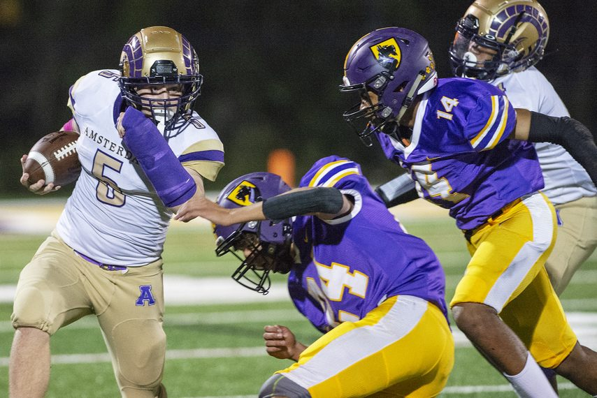 Amsterdam's Matthew Miller with the ball against Ballston Spa's Scott Dufore and Shomari White during a high school football game at Lynch Literacy Academy on Friday.