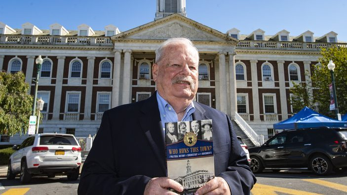 Author B. Donald Ackerman holds his book in front of Schenectady City Hall Thursday.