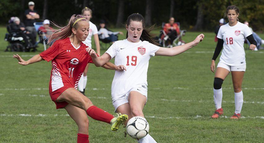 Guilderland's Paige Miller kicks the ball away in front of Mechanicville's Marissa Krosky Saturday afternoon at Guilderland High School, October 9, 2021.