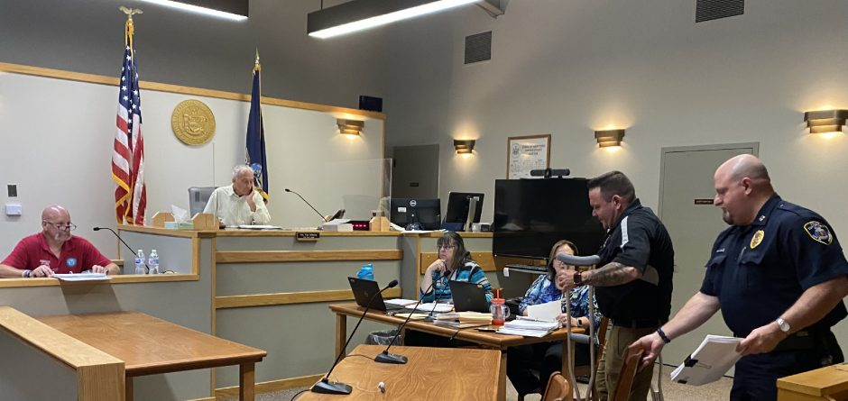 """Gloversville Police Chief Anthony """"Tony"""" Clay, on crutches, prepares to sit down for the Common Council's budget hearing while Councilman-at-large William Rowback Jr. and Mayor Vince DeSantis, both at left, look on. At right, Police Captain Mike Garavelli, also a PhD candidate, lends a hand."""