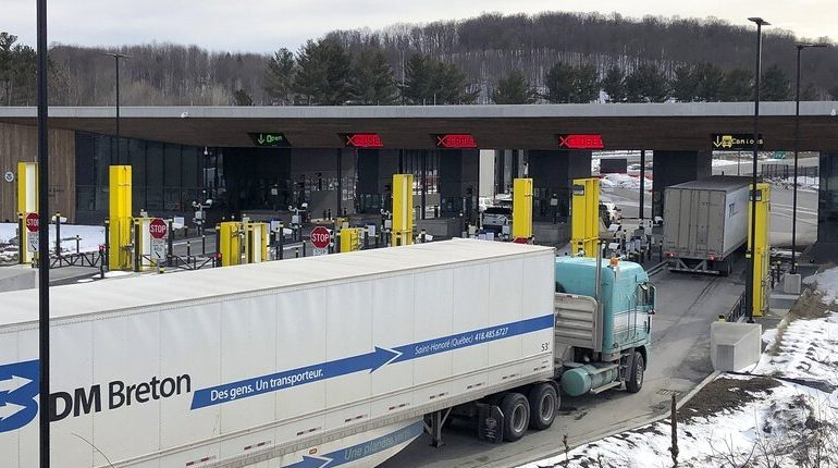 In this March 18, 2020 file photo, truck traffic from Canada waits to cross the border into the United States in Derby Line Vt.
