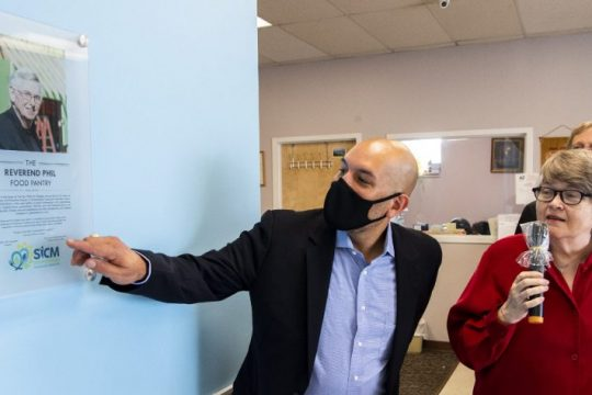 The Rev. Amaury Tanon-Santos, left, the CEO of SiCM, reads the plaque naming The Reverend Phil Food Pantry to his wife, Jan Grigsby, at the unveiling at the SiCM Pantry at 839 Albany St. on Friday.
