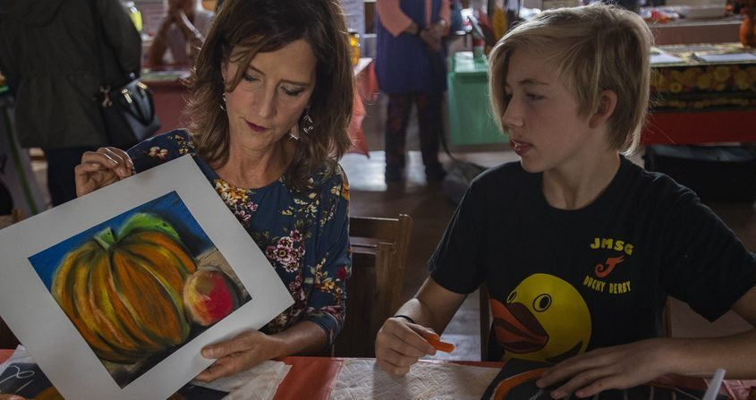 Michelle Egelston, left, teaches Ewan Ford, 14, of Amsterdam, the art of pastel drawing at the Glen Fall Fest on Saturday.