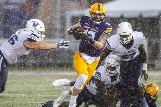 UAlbanyquarterback Jeff Undercuffler runs up the middle between Villanova's Jared Nelson, left, and Jalen Howard during Saturday's CAA football game at Tom & Mary Casey Stadium in Albany.