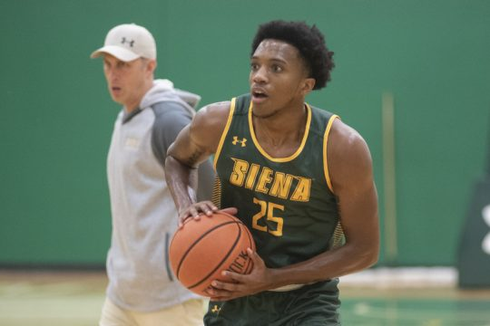 Aidan Carpenter looks up at the basket during a drill with head coach Carm Maciariello watching behind him during the first day of Siena men's basketball practice on Oct. 4, 2021.