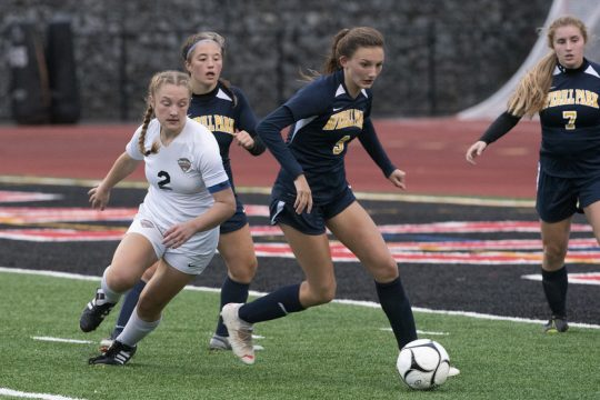 Mohonasen's Courtney Bush (2) advances toward the ball against Averill Park's Madisyn Locci, right, during the Section II Class A girls soccer semifinals at Mechanicville High School Monday.